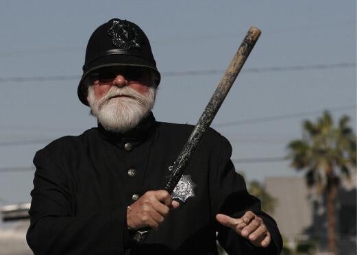 Ein englischer Polizist mit Knüppel schaut böse